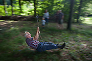 A pensioner blurs across woodland during a home-made zip wire ride on private land in Somerset. The old but sprightly and active gentleman keeps his legs straight to avoid scraping them along the woodland floor and stopping him before the end of the short ride. In the background are members of his family of varying ages, encouraging and laughing as he sweeps past on this bright summer afternoon.