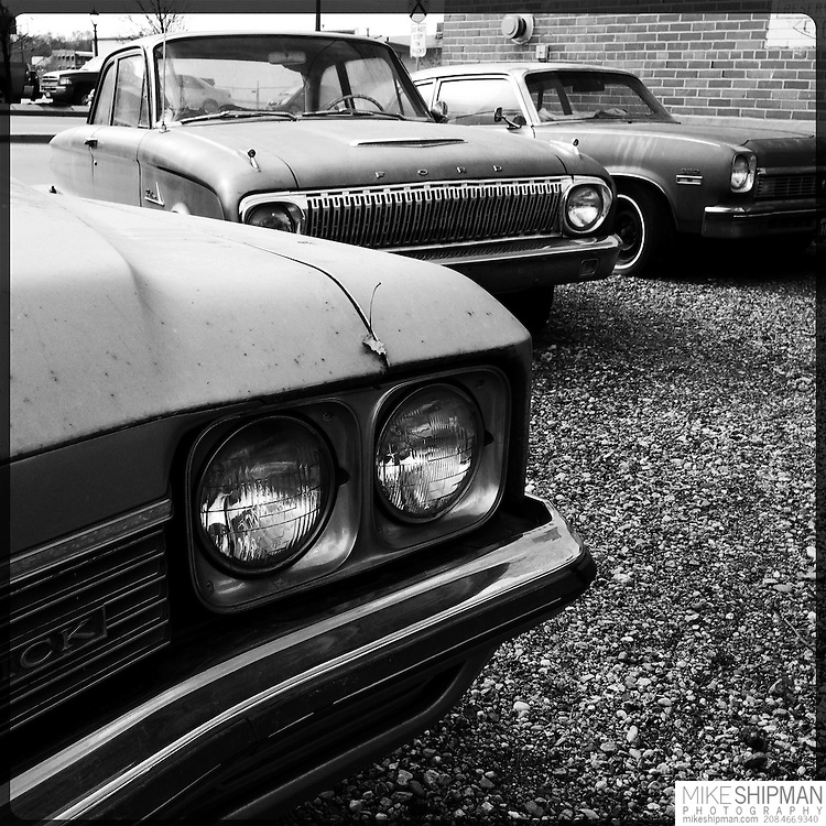Three late model cars parked in the lot of an auto repair shop