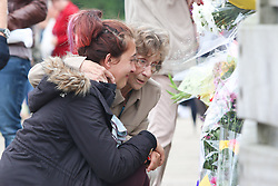 © Licensed to London News Pictures. 29/08/2015. Shoreham, UK.  A woman can be seen comforting a younger woman she didn't knew at the Toll bridge in Shoreham where thousands of flowers have arrived over the last week  since the plane crash of the Hawker Hunter T7 jet on Saturday August 22nd what killed 11 people. Today a one minute silence was held on the bridge attended by Thousands of people, Today August 29th 2015. Photo credit : Hugo Michiels/LNP