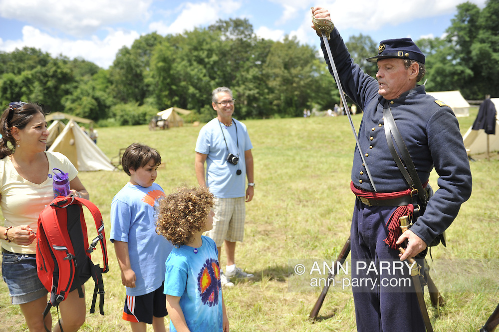 Old Bethpage, New York, USA - July 21, 2012: At far right, WILLIAM (BILL) CARMAN of Wantagh, NY, whose great-grandfather, John Carman, was member of Co. H in Civil War, draws his sword from sheath, during re-creation of Life in Camp Scott, a Union Army training camp, at Old Bethpage Village Restoration, to commemorate 150th Anniversary of American Civil War, on Saturday, July 21, 2012.