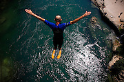"""Adem Mocca Pajevic jumps from the top of the Old Bridge on a 39* C (102* F) day into water that is around 10* C (50* F), a shock to the system that compounds the 20meter (66 feet) fall...Divers and tourists at Mostar's famous Old Bridge (Stari Most) in Bosnia and Herzegovina. This bridge is the city and region's biggest tourist attraction and there are busses full of tourists coming in from Sarajevo and Dubrovnik, Croatia. For 25euros tourists can train to jump from the bridge themselves, under supervision from the """"professional"""" Mostar divers known as the Mostari. .."""