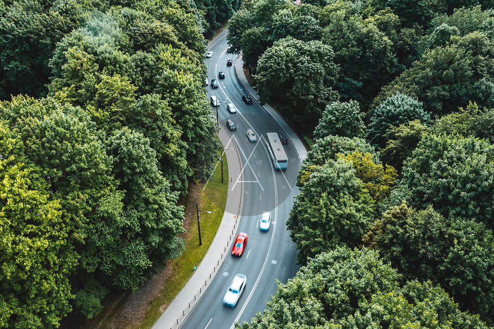 Aerial view of city traffic on curved road between green trees in Kaunas, Lithuania