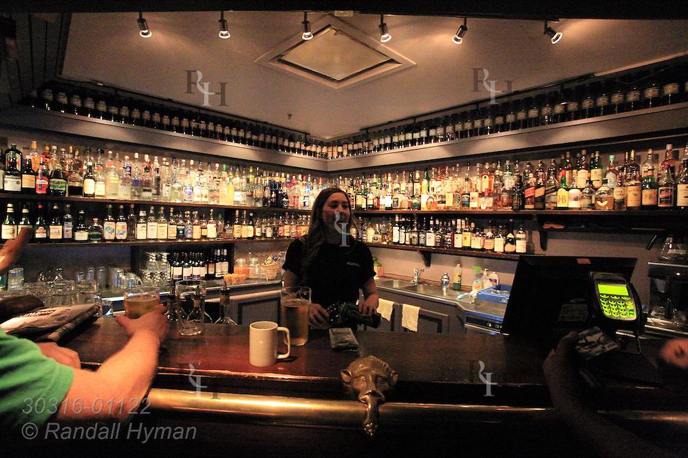 Barmaid serves patrons at Karlsberger Pub in Longyearbyen, Svalbard, Norway.