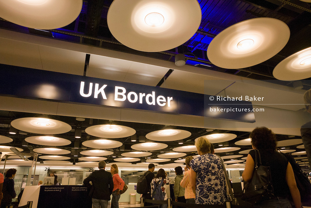 """Queues of newly-arrived airline passengers line up to await their turn at the UK Border Agency's passport control at Heathrow Airport's Terminal 5. Immigration officers deal with each member of the public seeking entry into the United Kingdom but on average, 10 a day are refused entry at this London airport and between 2008 and 2009, 33,100 people were detained at the airport for mainly passport irregularities. The UK Border Agency is responsible for securing the United Kingdom borders and controlling migration in the UK. They manage border control enforcing immigration and customs regulations and also consider applications for permission to enter or stay in the United Kingdom, citizenship and asylum. From writer Alain de Botton's book: """"A Week at the Airport: A Heathrow Diary"""" (2009)."""