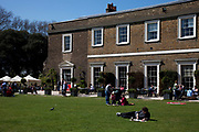 People gather on the lawn at Fulham Palace, West London.  The estate was owned by the Bishops of London for over 1300 years and the Palace was their country home from at least the 11th century. Vacated by the Bishops in 1975, the Palace is now managed jointly by Hammersmith and Fulham Council and the Fulham Palace Trust.