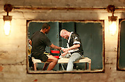 An MMA fighter and his trainer are reflected in a mirror as he gets his hands taped up for a match.