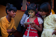 Poonam, 10, (centre) is playing a game on the new generation smartphone belonging to Neelam, 32, Alex Masi's translator, while Jyoti, 11, (right) Poonam's sister, and Ravi, 12, (left) their older brother, are watching over, eager to try. The children now live in a newly built home in Oriya Basti, one of the water-contaminated colonies in Bhopal, central India, near the abandoned Union Carbide (now DOW Chemical) industrial complex, site of the infamous '1984 Gas Disaster'. After being in constant touch with the family since 2011, Neelam has become a trusted friend to rely on for any serious problem or advice.