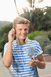 Portrait male teenager listening music MP3 player
