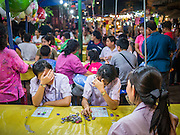 """27 NOVEMBER 2012 - BANGKOK, THAILAND: School girls react to losing a round of bingo in the Bingo tent at the Wat Saket Temple Fair in Bangkok. Bingo is called Bingo in Thailand. Wat Saket, popularly known as the Golden Mount or """"Phu Khao Thong,"""" is one of the most popular and oldest Buddhist temples in Bangkok. It dates to the Ayutthaya period (roughly 1350-1767 AD) and was renovated extensively when the Siamese fled Ayutthaya and established their new capitol in Bangkok. The temple holds an annual fair in November, the week of the full moon. It's one of the most popular temple fairs in Bangkok. The fair draws people from across Bangkok and spills out in the streets around the temple.    PHOTO BY JACK KURTZ"""