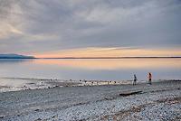 Two female teenagers enjoying a cobblestone beach along Bellingham Bay at sunset, Bellingham Washington USA