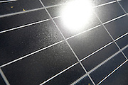 Close-up of a photovoltaic solar energy panel with reflection of the sun. This panel, or module, is made up of photovoltaic (PV) cells. PV cells convert sunlight into electrical energy. Photovoltaic panels are an economical, efficient way to produce electricity that does not pollute or contribute to global warming.