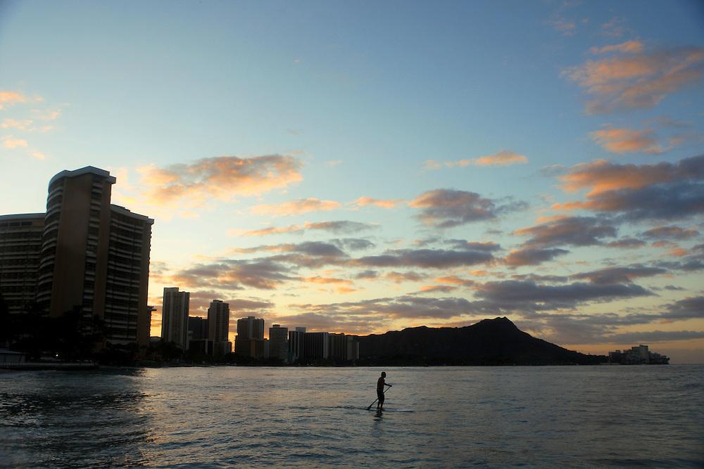 A long boarder takes to the sea as the sun rises over Diamond Head Crater near Waikiki Beach.