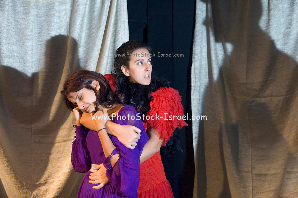 2 women hugging each other while fearing a large unknown shadow