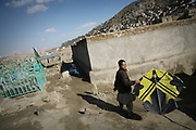 """Yassin, 9, the second son of Noor Agha, brings a kite with a scorpion emblem with a writing that say, """"Noor Agha, the son of the Scorpion,"""" to his house in the middle of a cemetery, Kabul, Afghanistan, Tuesday, March, 6, 2007. Noor Agha is a renowned kite maker who made kites for the movie makers of the best-selling novel, The Kite Runner, which will be distributed by Dreamworks and Paramount Vantage in Nov. this year. Noor Agha's wives, using their special glue, help him produce enough kites to please the clients' needs. Some of his children can also make their own kites with plastic bags and bamboo sticks. As the Afghan New Year's Day (Nawruz) approaching on March 21, the finger tips of Noor Agha's family got busier for mass production."""
