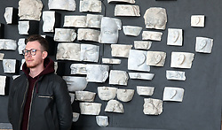 May 2, 2019 - Kyiv, Ukraine - A visitor of the Renovation modern art exhibition poses for a picture with fragments of plaster faces in the background at the River Port of Kyiv, capital of Ukraine, May 2, 2019. Ukrinform. /VVB/ (Credit Image: © Hennadii Minchenko/Ukrinform via ZUMA Wire)