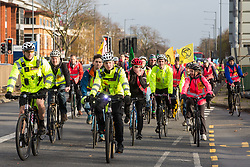 London, UK. 8 December, 2019. Climate activists from Extinction Rebellion arrive at Heathrow airport from Hyde Park on a Critical Mass bicycle ride to attend a Bikes Against Bulldozers protest against Heathrow expansion and the greenwashing of climate commitments by political parties. The activists staged a lie-in in front of a realistic full-scale mock-up of a bulldozer to which Boris Johnson and John McDonnell were invited in order to fulfil their pledge of lying down in front of bulldozers to be used for Heathrow expansion.