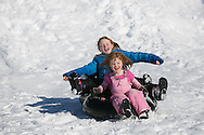 Needham, MA 02/10/2013<br /> Annie O'Brien, age 4, sleds down the hill behind Needham High School on a tube with her sisters Maggie, age 8, and Kate, age 10, on Sunday afternoon.