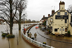 © Licensed to London News Pictures. 17/02/2014; Upton on Severn, Worcestershire, UK.  Soldiers patrol flood defences. The river Severn is high at Upton on Severn, but the flood defences have kept the town from flooding.  The army are helping to check the flood defences and transport people to nearby villages cut off by floods.<br /> Photo credit: Simon Chapman/LNP