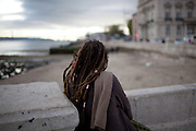 A young woman looking at the sunset over the Tagus river, at Praça do Comércio in the Baixa district, in central Lisbon.