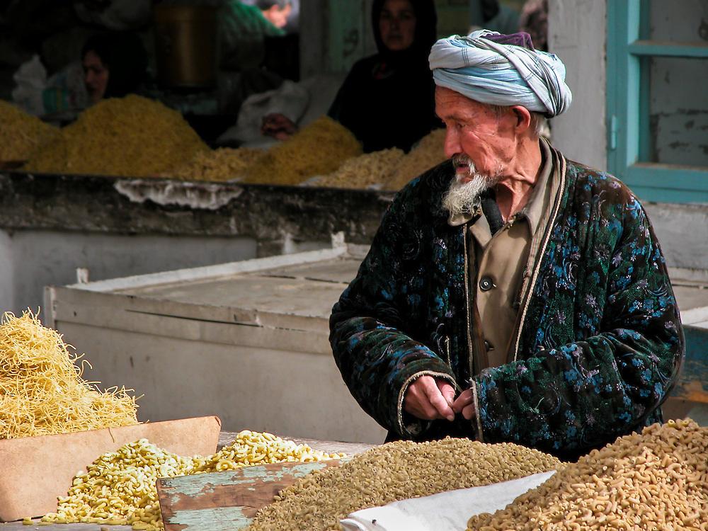 Portrait of an old Tajik man looking over the pasta for sale in a market in western Tajikistan