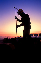 Stock photo of a man working at sunset at a CO2 fracking site