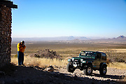 Man takes a cigarette break after off-roading in his Jeep Wrangler
