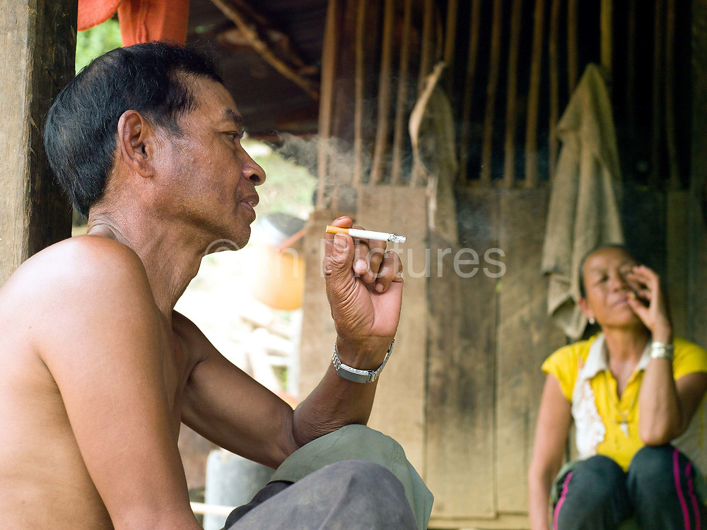 A Khmu man and his wife sit outside their home relaxing and smoking cigarettes in the remote and roadless Khmu ethnic minority village of Ban Phatao, Phongsaly province, Lao PDR. Ban Phatao will soon be temporarily relocated away from the Nam Ou river due to the construction of the Nam Ou Cascade Hydropower Project Dam 5.