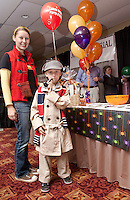 "Morgan Dube along with her son Troy as ""Sherlock Holmes"" make a stop at  the Lakes Region Party and Gifts table as they set out to investigate over 85 Lakes Region area businesses gathered at the 2011 Business BooFest at Opechee Inn and Spa Conference Center on Thursday evening.  (Karen Bobotas/for the Laconia Daily Sun)"
