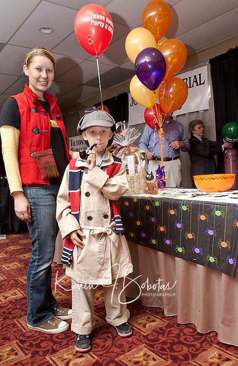 """Morgan Dube along with her son Troy as """"Sherlock Holmes"""" make a stop at  the Lakes Region Party and Gifts table as they set out to investigate over 85 Lakes Region area businesses gathered at the 2011 Business BooFest at Opechee Inn and Spa Conference Center on Thursday evening.  (Karen Bobotas/for the Laconia Daily Sun)"""