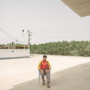 Sakir Ali is a clerk at a gas station. He sits in the shade waiting for a client, it is 47 degrees C.