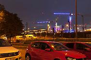 illuminated cranes on the the construction site of the building project MesseCity Koeln near the exhibition center in the district Deutz, in front of it the parking place of the railway station Deutz, Cologne, Germany.<br /> <br /> beleuchtete Kraene auf der Baustelle des Grossprojektes MesseCity Koeln neben dem Messegelaende, davor der Parkplatz des Bahnhofs Deutz, Koeln, Deutschland.