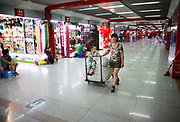 A woman pulls a cart carrying her son as well as sacks of goods through the Yiwu International Trade City in Yiwu, Zhejiang Province, China on Sunday, 11 September 2011.   As the trading hub for small and medium manufacturers and exporters in the Yangtze River Delta region, Yiwu faces an uncertain future as export orders decline due to the slow economic recoveries of China's two largest trading partners, Europe and the United States