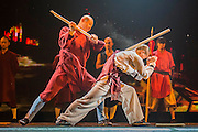"""A monk has a stave broken on his back - Twenty Shaolin monks, from their  temple in the foothills of the Song Shang mountain range in China's Henan province, take to the stage to demonstrate their martial arts expertise in an 'awe-inspiring' performance. SHAOLIN is a display of theatre and physical prowess in which the cast perform """"superhuman"""" feats. The show combines traditional Shaolin Kung Fu, inch perfect choreography with dramatic lighting and sound that evokes the spirit of their tradition – their Temple being the birthplace of Kung Fu.  These are the very best Shaolin Kung Fu experts on the planet and they have come together to create this show. The Shaolin Monks are lifted aloft on sharpened spears, break marble slabs with their heads, perform handstands on two finger tips,splinter wooden staves with their bodies, break bricks on their heads and fly through the air in a series of incredible back flips. The show embarks upon a three-week run at The Peacock Theatre, London from 29 September – 17 October 2015."""