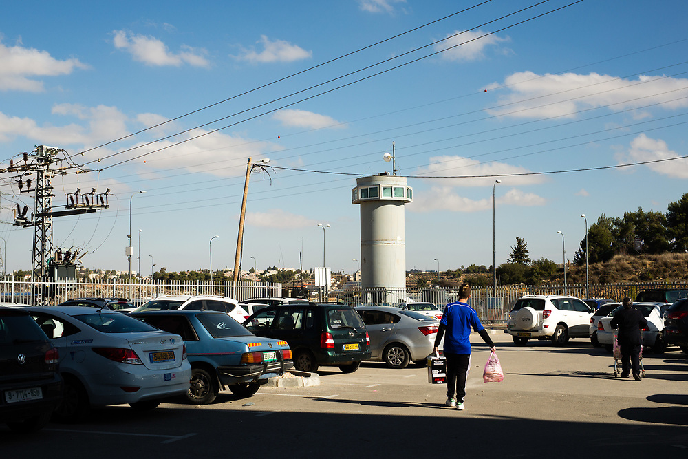 An Israeli military watchtower is seen behind Jewish customers carrying groceries to their cars in the parking lot of a recently opened shopping center located at the Gush Etzion junction, near the West Bank Jewish settlement of Efrat in the Gush Etzion settlement bloc, which is situated on the southern outskirts of the Palestinian West Bank city of Bethlehem, on December 30, 2016.