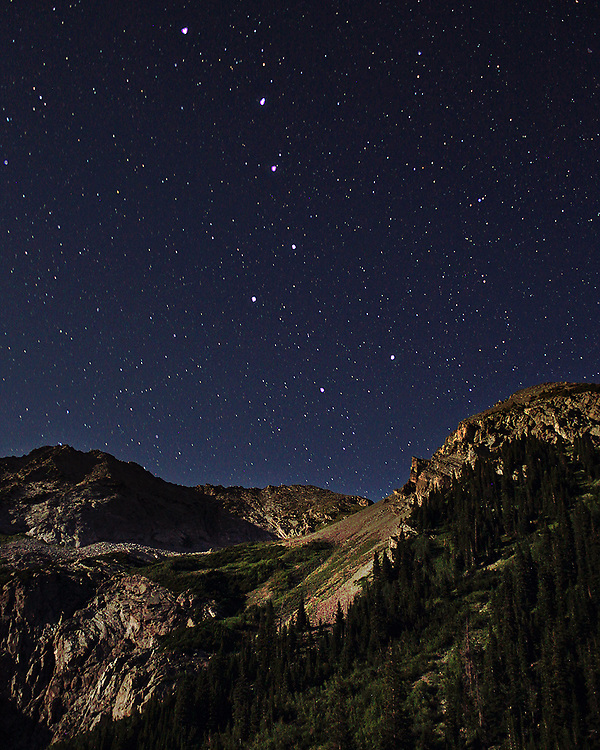The Big dipper (Ursa Major) setting over the Rocky Mountians. The landscape is illuminated by the moon.