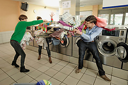 Man and women are fooling around with laundry