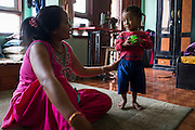 Nanimaiya Tamang (31) speaks with her nephew Sujal Tamang (2) who is now living with her in her apartment in Jorpati, Kathmandu, Nepal on 2 July 2015. Sujal was buried under the rubble of his collapsed house for 36 hours before rescuers found him injured with a broken leg next to his mother who was killed on the spot. Photo by Suzanne Lee for SOS Children's Villages