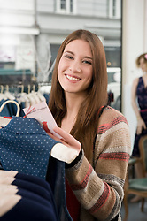 Portrait of young woman shopping in fashion store, smiling