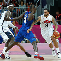 29 July 2012: USA Deron Williams drives past Florent Pietrus of France during the 98-71 Team USA victory over Team France, during the men's basketball preliminary, at the Basketball Arena, in London, Great Britain.