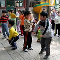 Asia, China, Beijing. Kindergarten school children having physical fitness.