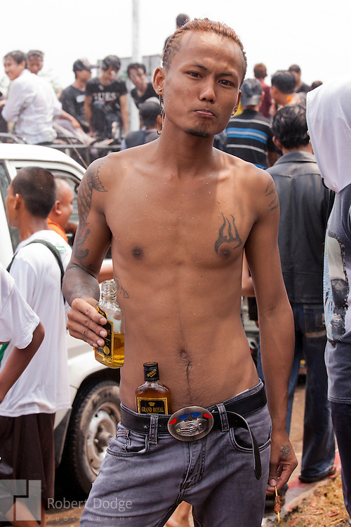 Mandalay, Myanmar- April 14, 2013: This young man looks like he is ready to party. Indeed, there is plenty of drinking during Myanmar's Thingyan Water Festival, also shared some affection with their friends as they celebrated the New Year. Thingyan is held in April, one of the hottest months of the year in Myanmar. The water festival marks the country's New Year celebration and the festival includes lots of drinking, singing, dancing and theater. Wherever you are you are likely to get doused with water as the Burmese see this as a cleansing of the previous year's sins and bad luck and a blessing for good luck and prosperity in the year ahead. In the major cities of Mandalay and Yangon, large platforms are erected along major roadways and are equipped with high powered water hoses. The platforms, sponsored by large corporate donors, also have dance stages and play the latest pop and hip hop music. Thousands of residents pour into the streets by foot, motorbike and flatbed truck to get hosed under the platforms while they drink and dance. Many of the young celebrants wear their best clubbing clothes. And many of the party goers are men, having left their wives and girlfriends at home.