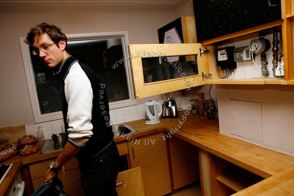 Marc Kouffman, 22, working for Bio Regional Development Group is portrayed while inside the kitchen of a house on show in the BedZED housing complex on Thursday, Sep. 6, 2007, in London, UK. All the energy consumption meters are easy to find and to check and are located in the kitchen cupboard. BedZED or the Beddington Zero Energy Development, is an environmentally-friendly housing development near Wallington, England in the London Borough of Sutton. It was designed by the architect Bill Dunster who was looking for a more sustainable way of building housing in urban areas in partnership between the BioRegional Development Group and the Peabody Trust. There are 82 houses, 17 apartments and 1,405 square meters of work space were built between 2000. The project was shortlisted for the Stirling Prize in 2003. The project is designed to use only energy from renewable source generated on site. In addition to 777 square meters of solar panels, tree waste is used for heating and electricity. The houses face south to take advantage of solar gain, are triple glazed and have high thermal insulation while most rain water is collected and reused. Appliances are chosen to be water efficient and use recycled water wherever possible. Low impact building materials were selected from renewable or recycled sources and were all originating within a 35 mile radius of the site to minimize the energy required for transportation. Also, refuse collection facilities are designed to support recycling and the site encourage eco-friendly transport: electric and LPG cars have priority over petrol/diesel cars, and electricity is provided by parking spaces appositely built for charging electric cars.