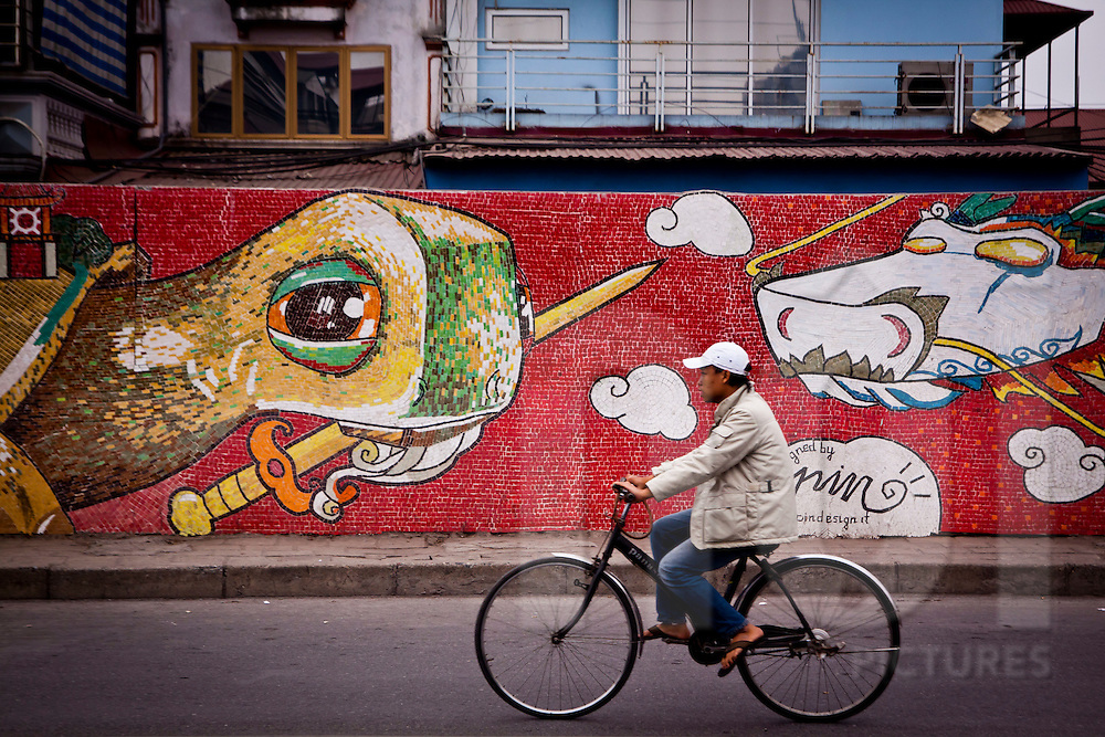 A man cycles past the 1000 Year Anniversary mosaic in Hanoi, Vietnam