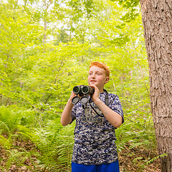 A boy bridwatching in a forest at the Donibristle Reservation in Topsfield, Massachusetts.