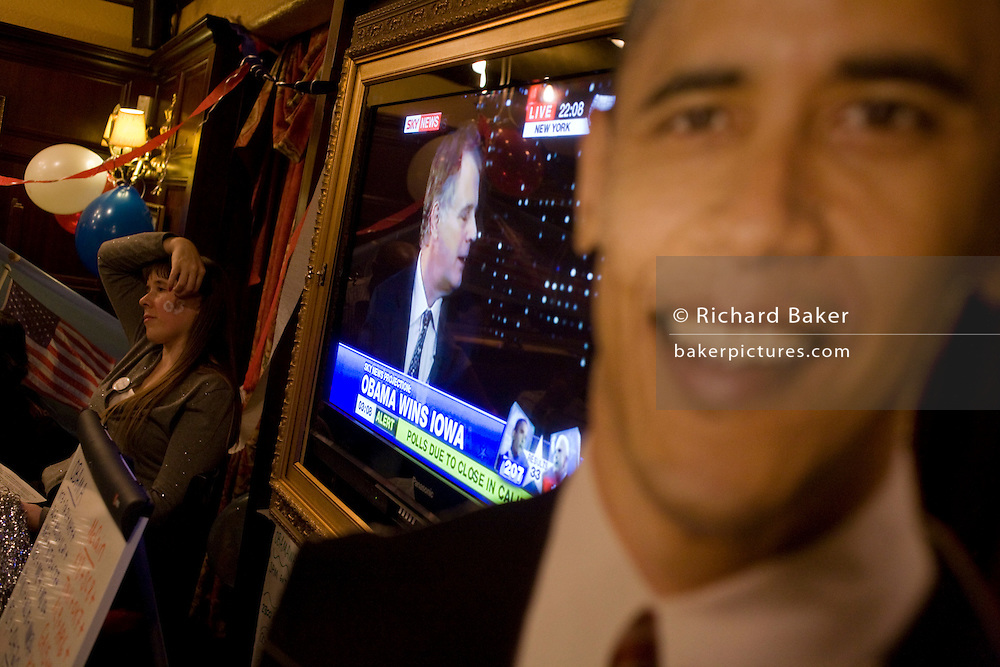 In London England, a life-size cardboard cut-out of Barack Obama stands next to a SKY News TV screen that is broadcasting live the latest polls of the 2008 US presidential elections. A Democratic party supporter listens intently and reacts with the tension of the early polls that suggest Obama is doing well against his Republican adversary, John McCain in this historic political election which saw the election of America's first black Commander in chief. The location is a pub called the Hoop and Toy, in South Kensington, West London which has been opened all night for this special event for the American expatriate community living in this European capital.