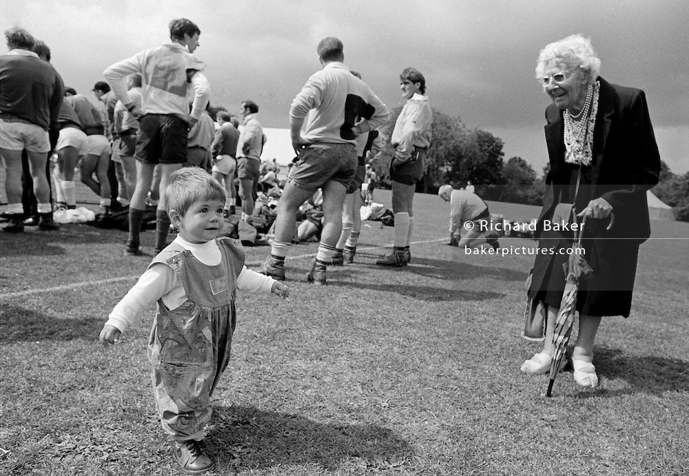 """Crooked Lady."" A twelve month-old girl who has recently learned to walk proudly strides past an elderly lady with balancing arms outstretched while at the Dulwich Show in South London. There is a marked difference between the youthful, upright posture of the young girl to the hunched and bent stance of the old woman who stands supporting herself on a brolley. It is a picture that compares youth with old age, the delight that a person of later years shows to a child whose life reaches far ahead. This is from a documentary series of pictures about the first year of the photographer's first child Ella. Accompanied by personal reflections and references from various nursery rhymes, this work describes his wife Lynda's journey from expectant to actual motherhood and for Ella - from new-born to one year-old."