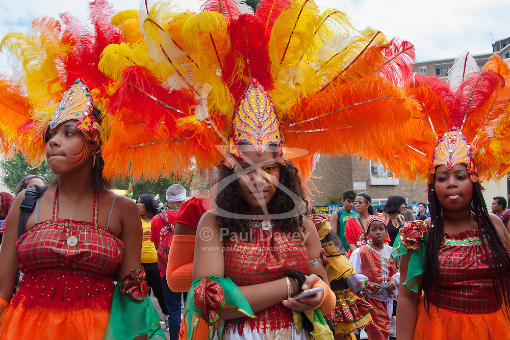 """London, August 24th 2014. Girls wait for the stop-start procession to get moving againas thousands of Londoners of all races and cultures attend Notting Hill Carnival's """"Family friendly"""" day ahead of the main carnival on August Bank Holiday Monday."""