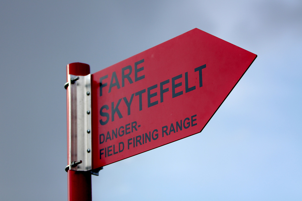 Skilt som signaliserer fare med bakgrunn i nærliggende skytefelt.