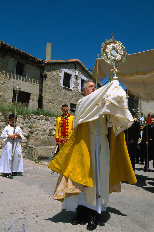 Holding the monstrance with the host, the priest leads the congregation in a procession through the village streets during the Fiesta del Colacho, in Castrillo de Murcia, Burgos province, Spain. The Fiesta del Colacho is held every year at the time of the Catholic feast Corpus Christi.