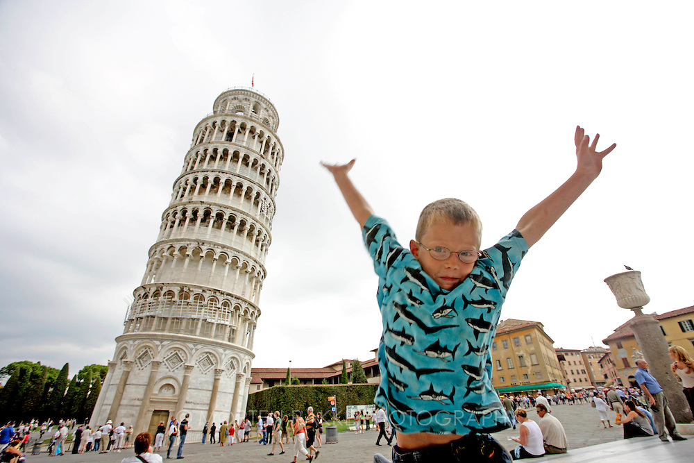 Young boy jumps in front of The Leaning Tower of Pisa, Italy